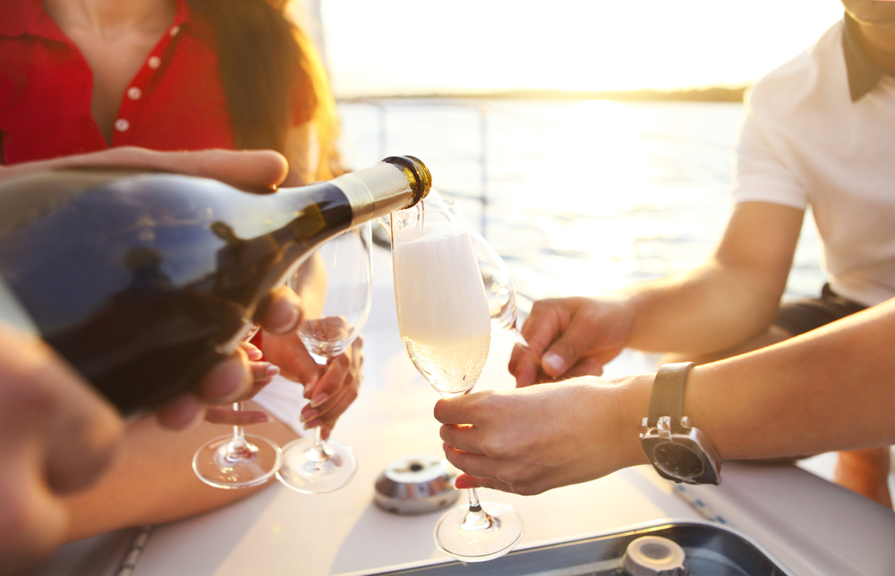 A group of friends pouring champagne on a yacht